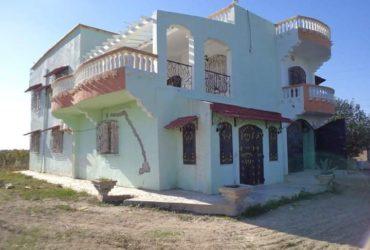 Une ferme à vendre avec une villa à deux étages et une maison pour le gardien